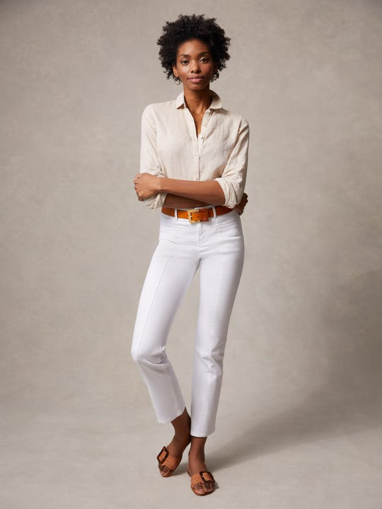 Model wearing J.McLaughlin Emmie Jeans in white made with denim fabric.