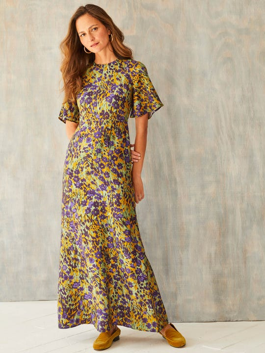 Model wearing J.McLaughlin Giovanna dress in marigold/multi cow made with silk viscose twill.