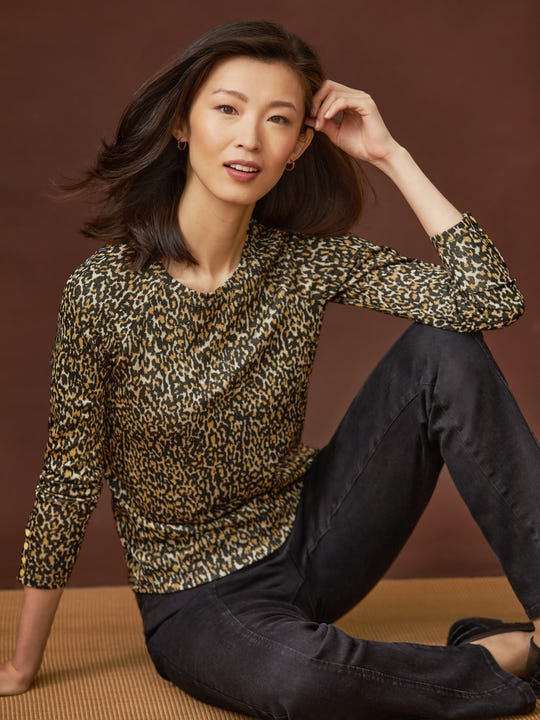 Model wearing J.McLaughlin Jana top in off taupe/black made with viscose.