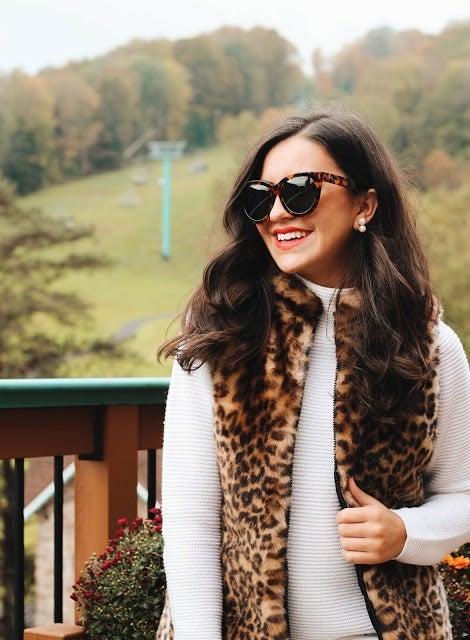 smiling woman in leopard vest